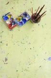 La bandeja del color contiene diverso color de mezcla con la brocha Foto de archivo