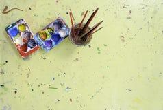 La bandeja del color contiene diverso color de mezcla con la brocha en agua Imágenes de archivo libres de regalías