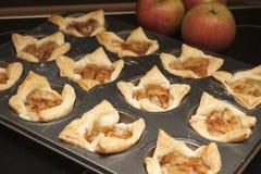 La bandeja del horno de galletas cocidas llenó de las rebanadas de manzanas rojas, cubiertas con el azúcar de formación de hielo  Imagen de archivo