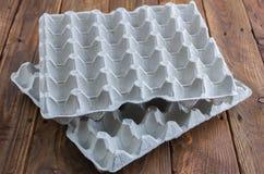 La bandeja del huevo de la cartulina en la tabla de madera Imagen de archivo libre de regalías