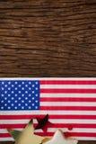 La bandera americana y la estrella forman la decoración dispuesta en la tabla de madera Fotos de archivo libres de regalías