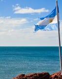 La bandera de Argentina con el mar azul en el fondo Fotografía de archivo