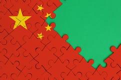 La bandera de China se representa en un rompecabezas terminado con el espacio verde libre de la copia en el lado derecho fotografía de archivo libre de regalías