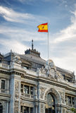 La bandera de España que agita en el edificio del banco de España Imágenes de archivo libres de regalías