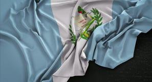 La bandera de Guatemala arrugó en el fondo oscuro 3D rinde Fotografía de archivo libre de regalías