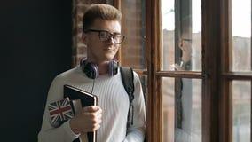 La bandera de Holding Great Britain del estudiante y hacer una pausa la ventana almacen de metraje de vídeo