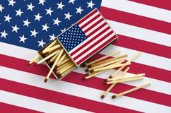 La bandera de los Estados Unidos de América se muestra en una caja de cerillas abierta, de la cual varios partidos caen y las men foto de archivo