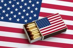 La bandera de los Estados Unidos de América se muestra en una caja de cerillas abierta, que se llena de los partidos y miente en  foto de archivo libre de regalías
