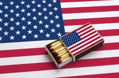 La bandera de los Estados Unidos de América se muestra en una caja de cerillas abierta, que se llena de los partidos y miente en  imagenes de archivo