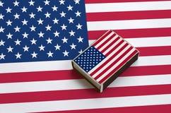 La bandera de los Estados Unidos de América se representa en una caja de cerillas que mienta en una bandera grande imagenes de archivo