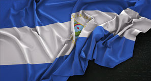 La bandera de Nicaragua arrugó en el fondo oscuro 3D rinde Fotografía de archivo libre de regalías