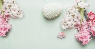 La bandera de Pascua con los jacintos y la decoración egg en el fondo de madera en colores pastel ligero, visión superior Foto de archivo libre de regalías