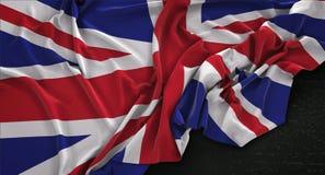 La bandera de Reino Unido arrugó en el fondo oscuro 3D rinde Fotos de archivo