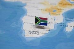 La bandera de Suráfrica en el mapa del mundo imágenes de archivo libres de regalías