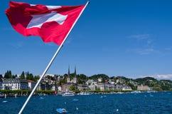 La bandera del suizo por el lago de Lucerna imagenes de archivo