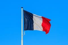 La bandera francesa con el cielo azul en el fondo Imagenes de archivo