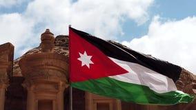 La bandera jordana vuela en viento tieso sobre la cámara lenta 2 del Hacienda del Petra almacen de video