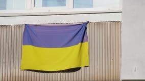 La bandera nacional de Ucrania se cuelga en el balcón del apartamento almacen de metraje de vídeo