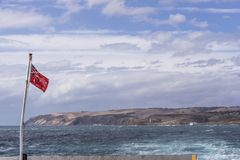 La bandera roja australiana que agita en el transbordador que conecta el cabo Jervis con Penneshaw, isla del canguro, Australia m imagenes de archivo