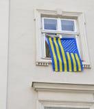 La bandiera è sospesa alla finestra Fotografia Stock