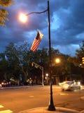 La bandiera americana pende dal palo della luce al crepuscolo Immagine Stock