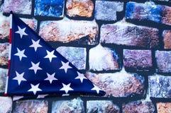 La bandiera degli Stati Uniti d'America ha piegato in un triangolo su un fondo del muro di mattoni immagini stock