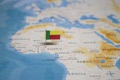La bandiera del Benin nella mappa di mondo fotografia stock