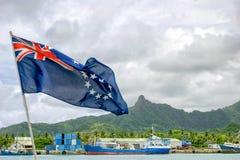 La bandiera del cuoco Islands ondeggia contro il paesaggio dell'isola Fotografia Stock