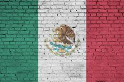 La bandiera del Messico è dipinta su un vecchio muro di mattoni immagini stock
