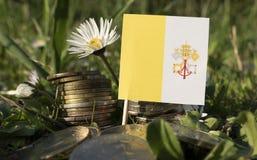 La bandiera del Vaticano con la pila di soldi conia con erba Fotografie Stock Libere da Diritti