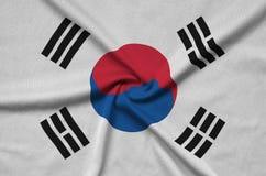 La bandiera della Corea del Sud è descritta su un tessuto del panno di sport con molti popolare Insegna dello sport di squadra fotografia stock