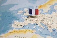 La bandiera della Francia nella mappa di mondo fotografia stock