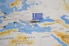 La bandiera della Grecia nella mappa di mondo fotografia stock libera da diritti