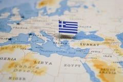 La bandiera della Grecia nella mappa di mondo immagini stock