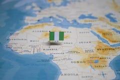 La bandiera della Nigeria nella mappa di mondo fotografie stock