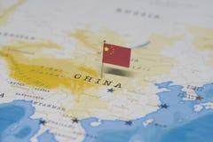 La bandiera della porcellana nella mappa di mondo fotografie stock
