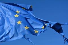 La bandiera della stella dell'Unione Europea dodici lacerata e con i nodi nel vento su cielo blu Fotografia Stock Libera da Diritti