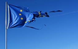 La bandiera della stella dell'Unione Europea dodici lacerata e con i nodi nel vento su cielo blu Fotografia Stock