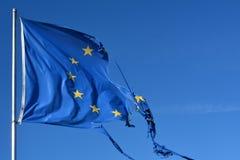 La bandiera della stella dell'Unione Europea dodici lacerata e con i nodi nel vento su cielo blu Immagine Stock
