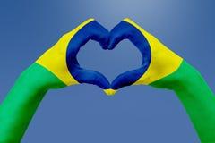 La bandiera delle mani del Brasile, modella un cuore Concetto del simbolo del paese, su cielo blu Fotografie Stock