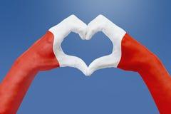La bandiera delle mani del Perù, modella un cuore Concetto del simbolo del paese, su cielo blu Fotografia Stock