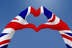 La bandiera delle mani del Regno Unito, modella un cuore Concetto del simbolo del paese, su cielo blu Fotografie Stock