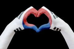 La bandiera delle mani della Corea del Sud, modella un cuore Concetto del simbolo del paese, isolato sul nero Fotografia Stock
