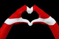 La bandiera delle mani della Danimarca, modella un cuore Concetto del simbolo del paese, isolato sul nero Fotografia Stock