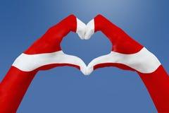 La bandiera delle mani della Danimarca, modella un cuore Concetto del simbolo del paese, su cielo blu Fotografia Stock Libera da Diritti
