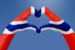 La bandiera delle mani della Norvegia, modella un cuore Concetto del simbolo del paese, su cielo blu Immagini Stock Libere da Diritti