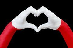 La bandiera delle mani della Polonia, modella un cuore Concetto del simbolo del paese, isolato sul nero Immagine Stock Libera da Diritti