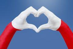 La bandiera delle mani della Polonia, modella un cuore Concetto del simbolo del paese, su cielo blu Fotografia Stock Libera da Diritti