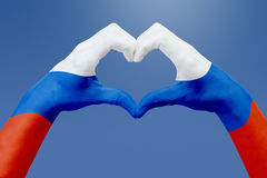 La bandiera delle mani della Russia, modella un cuore Concetto del simbolo del paese, su cielo blu Fotografia Stock