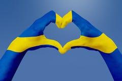 La bandiera delle mani della Svezia, modella un cuore Concetto del simbolo del paese, su cielo blu Fotografia Stock